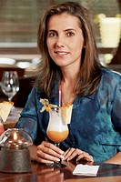 Portrait of a mid adult woman sitting in a restaurant and holding a glass of pina colada