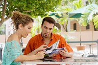 Close-up of a teenage girl and a mid adult man reading a magazine