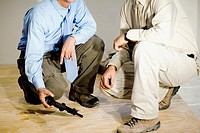 Low section view of two male architects crouching on a hardwood floor
