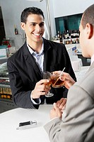 Close-up of two businessmen toasting with drinks in a bar