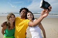 Young Man and Women Stand Side by Side on the Beach, Taking a Photograph of Themselves