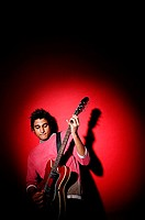 Young man playing guitar, standing against red background