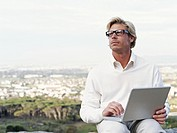Young man using laptop outdoors, cityscape in distance focus on man