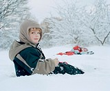 Boy 4-6 sitting in snow, smiling, portriat