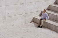 Man sitting on bottom step with laptop, eyes closed, elevated view