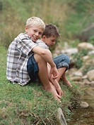 Two boys 9-11 sitting on river bank, smiling, portrait