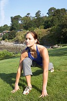 Young woman stretching, listening to MP3 player