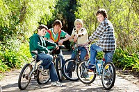 Four boys 9-13 on bikes, outdoors, portrait
