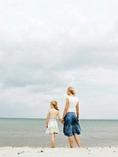 Mother and daughter 6-8 holding hands, standing on beach, rear view