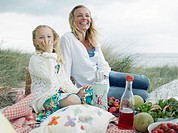 Mother and daughter 6-8 having picnic on beach, smiling