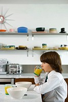 Boy 8-10 drinking orange juice in kitchen
