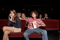 Teenage couple sitting in movie theatre auditorium