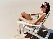 Young Woman in a Bikini Sitting on a Sun Lounger on a Beach