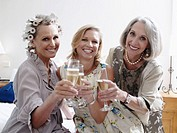 Three women toasting with champagne flutes, smiling, portrait