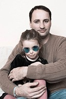 Young girl, wearing sunglasses, sitting with her father
