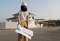 Female architect with plan looking at house in new development