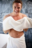 Young man holding towel in bathroom, smiling, portrait