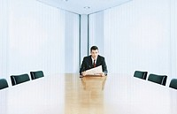Businessman sitting at boardroom table holding newspaper, portrait