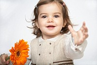 Toddler girl 18-21 months holding flower, arm outstretched, portrait