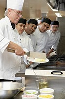 Group of students watching chef prepare food at culinary school