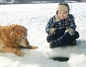 USA, Montana, Kila, boy 6-8 and dog ice fishing in Smith Lake