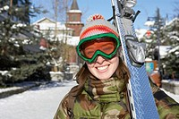 Young woman carrying skis, smiling, portrait