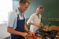 Mature couple cooking in kitchen, smiling