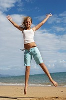 Blonde girl 9-11 jumping on sandy beach, arms up, smiling, portrait