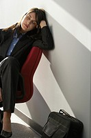 Young businesswoman sleeping on chair in lobby