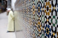 Morrocco, Fez, Medina, man leaning against tiled wall focus on tiles
