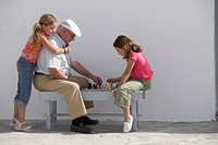 Grandfather playing chess with two granddaughters 8-10 outside house