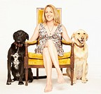 Mature woman sitting on chair between to Labrador retrievers, portrait