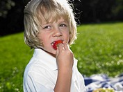 Boy 3-5 eating strawberry, outdoors, close-up