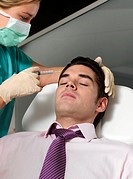 Nurse giving man cosmetic injection into face