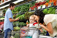 Parents with daughter 9-12 months in supermarket