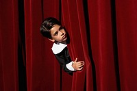 Boy 6-7 looking through stage curtains, portrait