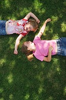 Two girls 5-8 lying on grass, laughing, elevated view