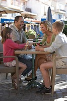 Family with daughter 7-9 and son 11-13 having drinks at outdoor restaurant, full length