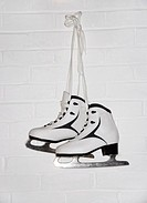 Ice skates hanging by wall