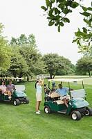 Two couples in golf buggies on golf course