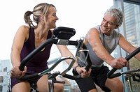 Mature man and woman on exercise bikes in gym, smiling, close-up