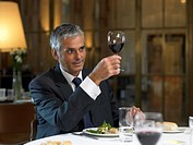 Mature businessman sitting at restaurant table, toasting with wineglass