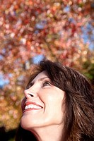 Woman looking upwards, smiling, low angle view