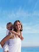 Woman giving son 10-12 piggyback, smiling, portrait