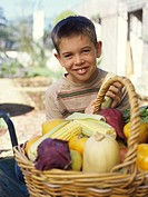 Boy 10-12 with wheelbarrow and basket of vegetables smiling portrait