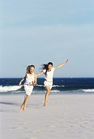 Two girls 10-12 running on beach, smiling