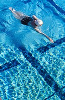 Senior woman swimming in pool, elevated view