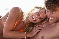 Young couple relaxing on beach, laughing, blonde woman wearing orange bikini, close-up, portrait