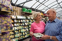 Senior couple shopping in garden centre, holding pack of flower bulbs, smiling