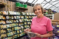 Senior woman holding flower bulbs in garden centre, smiling, portrait